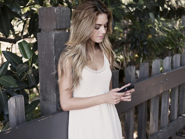 dívka s mobilem u plotu